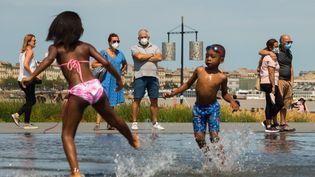 Des enfants jouent, sur la surveillance d'adultes portant le masque, à Bordeaux (Nouvelle-Aquitaine), le 15 août 2020. (LAURENT PERPIGNA IBAN / HANS LUCAS / AFP)