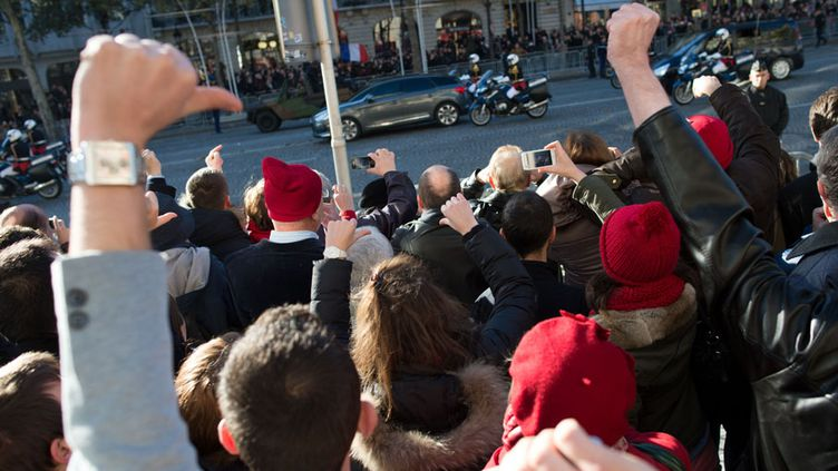 Des manifestants portant le bonnet rouge huent le président François Hollande à son passage lors du défilé commémoratif du 11-Novembre, à Paris. (LCHAM / SIPA)