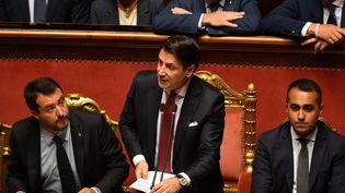 Le Premier ministre italien Giuseppe Conte (au centre), avec le ministre de l'Intérieur Matteo Salvini (à gauche) et le ministre du développement économique, du travail et des politiques sociales Luigi Di Maio (à droite), lors d'un discours solennel annonçant la fin du gouvernement de coalition, le 20 août 2019 à Rome (Italie). (ANDREAS SOLARO / AFP)