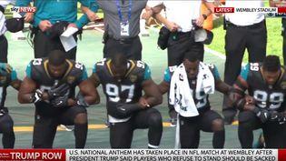 Des joueurs de la NFL (Fédérration de football américain) ont un génou à terre pendant la diffusion de l'hymne américain. (CAPTURE D'ÉCRAN Sky News)