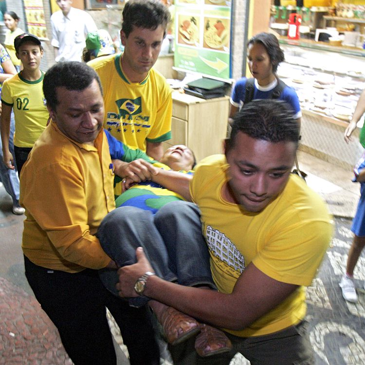Une supportrice victime d'une crise cardiaque, le 1er juillet 2006, à Rio de Janeiro (Brésil),pendant le quart de finale du Mondial entre la France et le Brésil, alors que les Bleus viennent d'ouvrir la marque. Admise à l'hôpital, elle en est sortie saine et sauve. (CAIO LEAL / AFP)