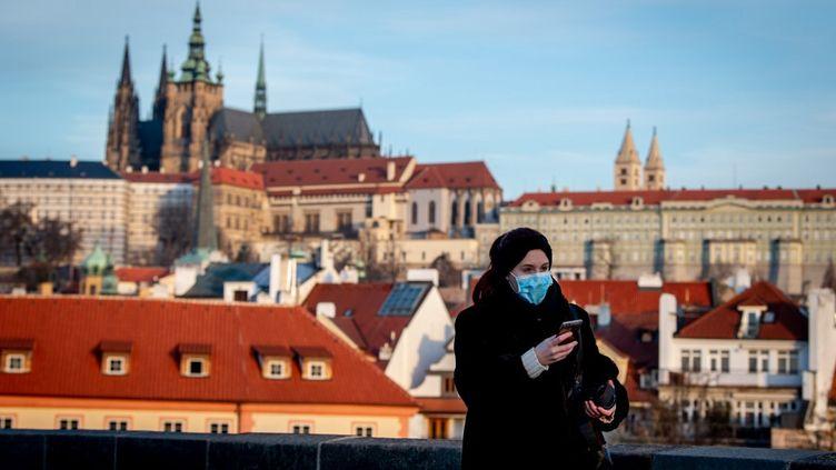 Une femme porte un masque contre le Covid-19 dans les rues de Prague, en République tchèque, le 16 mars 2020. (LUKAS KABON / ANADOLU AGENCY / AFP)
