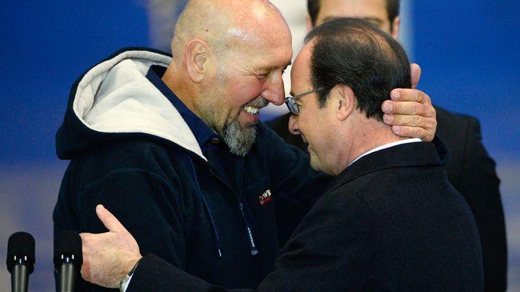 L'ex otage français, Serge Lazarevic (G) embrasse le président de la République française François Hollande sur l'aérodrome de Villacoublay (Yvelines), le 10 décembre 2014. (BERTRAND GUAY / AFP)