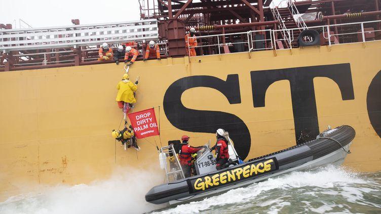 Des militants de Greenpeace manifestent sur un cargo qui s'apprête à amarrer à Rotterdam (Pays-Bas), samedi 24 novembre. (MARTEN  VAN DIJL / GREENPEACE NETHERLANDS)