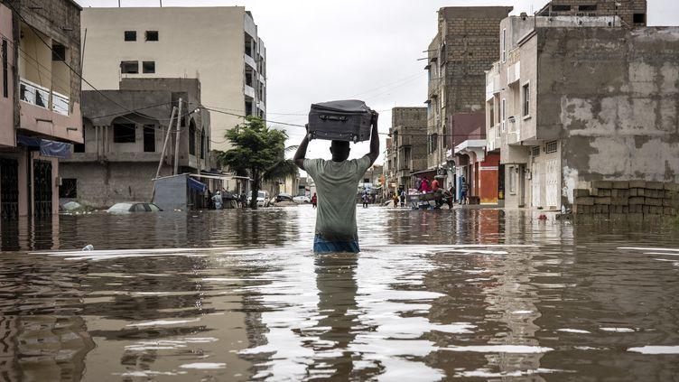 Un homme porte une valise alors qu'il déplace ses affaires hors de sa maison dans le quartier inondé de Keur Massar, à Dakar, le 20 août 2021. (JOHN WESSELS / AFP)