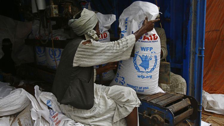 Un travailleur soudanais décharge l'aide du Programme alimentaire mondial (PAM) destinée au Soudan du Sud, à Port-Soudan, le 19 mars 2017. (ASHRAF SHAZLY / AFP)