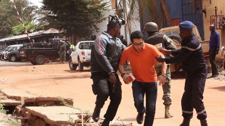 (Un client de l'hôtel Radisson évacué, ce vendredi © SIPA/AP/Harouna Traore)