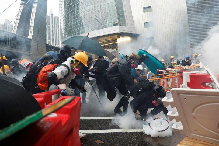 Des manifestants essuient des tirs de gaz lacrymogène de la police à Hong Kong, le 25 août 2019. (TYRONE SIU / REUTERS)