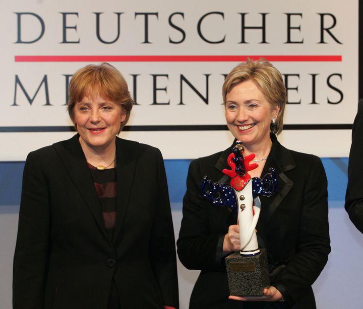 La sénatrice américaine Hillary Clinton et la présidente de la CDU allemande, Angela Merkel, en 2004, ensemble et en tailleur. (ULI DECK / DPA / AFP)