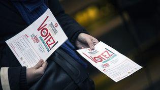 Un militant PS distribue des tracts, le 18 décembre 2016 à Paris, pour inciter les électeurs à aller voter à la primaire de la gauche. (ETIENNE LAURENT / EPA)