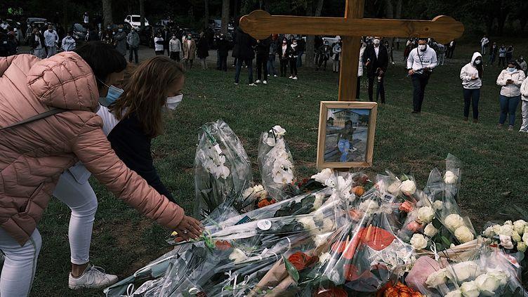 Des bouquets de fleurs devant la photo de Victorine Dartois, lors de la marche blanche organisée à Villefontaine (Isère), le 4 octobre 2020. (JEAN-PHILIPPE KSIAZEK / AFP)