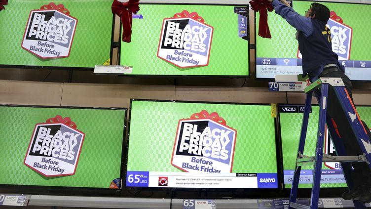 Un vendeur ajuste un ruban sur une télévision annonçant le Black Friday, à Los Angeles (Etats-Unis), le 24 novembre 2014. (JONATHAN ALCORN / REUTERS)