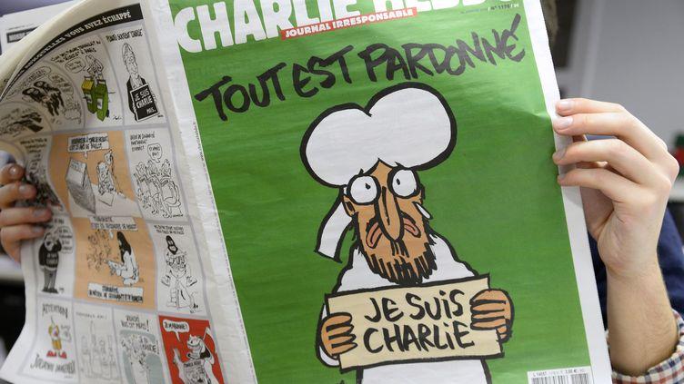 """Un lecteur parcourt le """"Charlie Hebdo"""" daté du 14 janvier 2015. (BERTRAND GUAY / AFP)"""