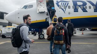 Des voyageurs montent dans leur avion pour le Royaume-Uni, depuis Nantes, en France, le 1er juillet 2020. (JULIEN MARSAULT / HANS LUCAS / AFp)