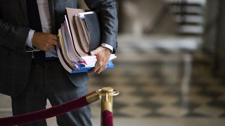 Un homme les bras chargés de dossiers à l'Assemblée. (JULIEN DE ROSA / MAXPPP)