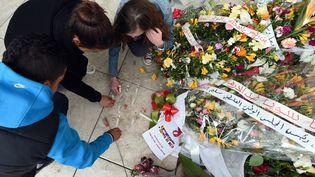 Des touristes allument des bougies devant le musée du Bardo à Tunis, en hommage aux victimes de l'attaque, le 27 mars 2015. (FETHI BELAID / AFP)