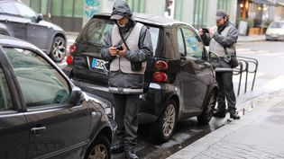 Des agents d'une autre société privée, Moovia, contrôlent le stationnement d'automobilistes à Paris, le 3 janvier 2018. (MAXPPP)