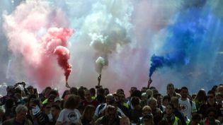 """Des fumigènes bleu, blanc, rouge, dans le défilé toulousain, qui a réuni plusieurs milliers de personnes, dont environ un tiers de """"gilets jaunes"""", le 1er mai 2019. (PASCAL PAVANI / AFP)"""