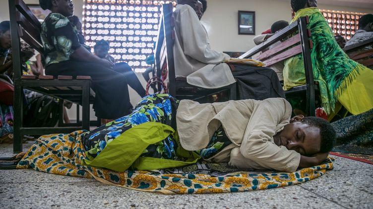 Une femme, couchée au sol, attend son tour pour prendre un rendez-vous à l'hôpital de Mulago qui vient de recevoir une nouvelle machine de radiothérapie le 19 janvier 2018, à Kampala, en Ouganda. Le centre hospitalier est un centre spécialisé dans le traitement du cancer qui accueille des patients de toute l'Afrique de l'Est. (SUMY SADURNI / AFP)