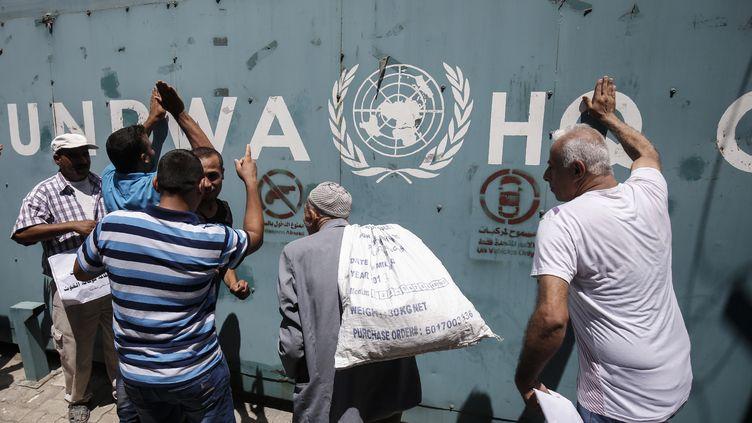 Des employés del'UNRWA protestent contre les suppressions de postes, devant les bureaux de l'agence de l'ONU, à Gaza le 31 juillet 2018. (SAID KHATIB / AFP)