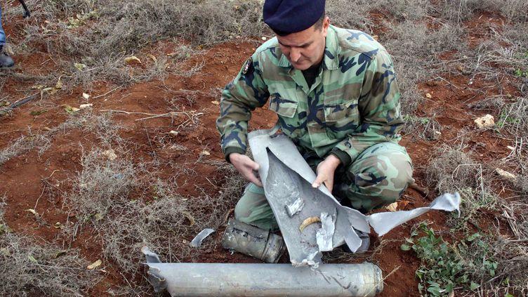 Un soldat libanais examinant un obus israélien, tiré dimanche 29 décembre 2013. (ALI DIA / AFP)