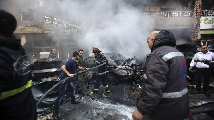 Des pompiers éteignent l'incendie provoqué par un attentat à la voiture piégée, dans la banlieue sud de Beyrouth (Liban), le 21 janvier 2014. (KHALIL HASSAN / REUTERS)