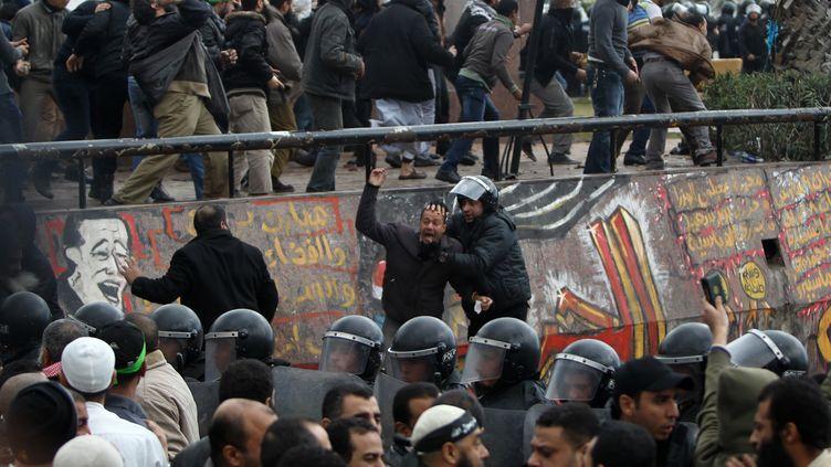 Des policiers s'interposent entre partisans et opposants au président égyptien Mohamed Morsi, le 21 décembre 2012 à Alexandrie (Egypte). (MAHMUD HAMS / AFP)