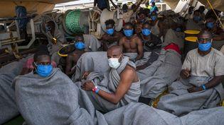 """Les migrants qui se trouvaient à bord du navire """"Louise Michel"""" juste après avoirété transférés sur le bateau humanitaire """"Sea Watch 4"""", au large des côtes maltaises, le 29 août 2020. (THOMAS LOHNES / AFP)"""