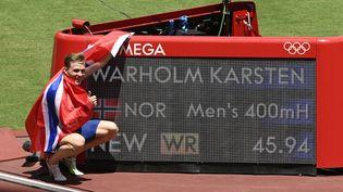 Le Norvégien Karsten Warholm pose près de son chrono en finale du 400 m haies des Jeux de Tokyo, après avoir établi un nouveau record du monde. (CROSNIER JULIEN / KMSP / AFP)