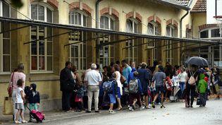 Des parents et des élèves dans une cour d'école. (Illustration). (/NCY / MAXPPP)