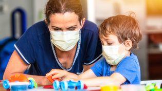 Un enfant joue avec une puéricultrice en pleine épidémie de Covid-19, aux Etats-Unis, le 19 mars 2020. (JUANMONINO / E+ / GETTY IMAGES)