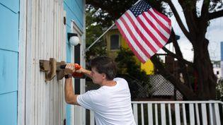 Un homme protègeun magasin àWrightsville (Caroline du Nord, Etats-Unis), à l'approche de l'ouragan Florence, le 11 septembre 2018. (LOGAN CYRUS / AFP)