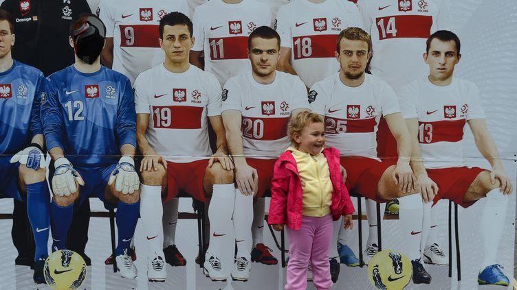 Un enfant pose à côté du poster de l'équipe nationale de Pologne, avant l'Euro 2012. (PATRIK STOLLARZ / AFP)