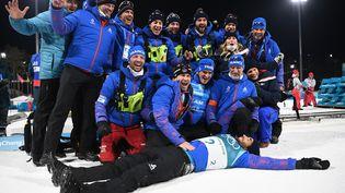 Martin Fourcade, entourédu staff de l'équipe de France de biathlon, savoure sa victoire sur la mass start (15 km) aux Jeux olympiquesdePyeongchang, le 18 février 2018. (FRANCK FIFE / AFP)