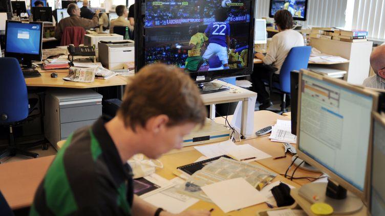 Des journalistes de l'AFP regardent un match entre le Japon et le Cameroun lors de la Coupe du monde 2010 en Afrique du Sud,le 14 juin 2010 à Paris. (FRED DUFOUR / AFP)