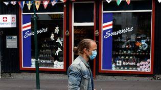 Un passant masqué devant un magasin de souvenirs aux couleurs du drapeau islandais à Reykjavik (Islande), le 3 septembre 2020. (JOHN SIBLEY / REUTERS)