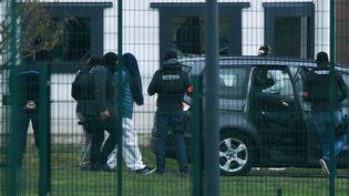 Une personne menottée est escortée par les forces de l'ordre, le 5 mars 2019, au centre pénitentiaire de Condé-sur-Sarthe (Orne). (JEAN-FRANCOIS MONIER / AFP)