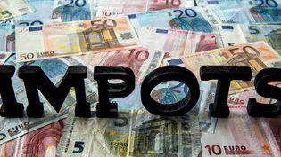 """Le mot """"IMPOTS"""" sur des billets de banque. (PHILIPPE HUGUEN / AFP)"""