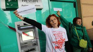 """Des membres d'Attac, lisant une """"scène de crime"""" devant une banque à Nice en novembre 2011 (AFP PHOTO / VALERY HACHE)"""