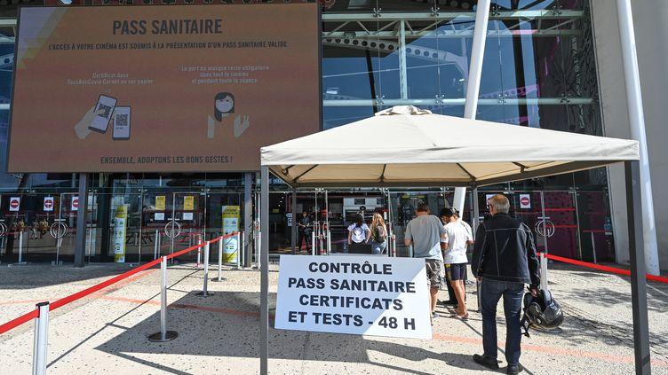 Des visiteurs présentent leur pass sanitaire à l'entrée du cinéma Gaumont multiplex Odyséum à Montpellier, le 29 juillet 2021 (PASCAL GUYOT / AFP)