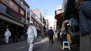 Une rue du quartier d'Itaewon, à Séoul (Corée du Sud), est désinfectée par des employés municipaux après une résurgence des cas de Covid-19. (YONHAP / AFP)