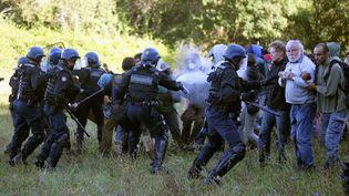 Des CRS entourant des opposants au barrage de Sivens, près de Lisle-sur-Tarn (Tarn), le 1er septembre 2014. (FLORINE GALEORN / AFP)
