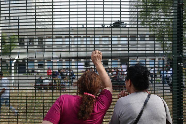 Deux femmes observent l'intérieur du lycéeoccupé par des migrants et le collectif La Chapelle en lutte, le 31 juillet 2015, à Paris. (CITIZENSIDE/ANTHONY DEPERRAZ / CITIZENSIDE.COM)