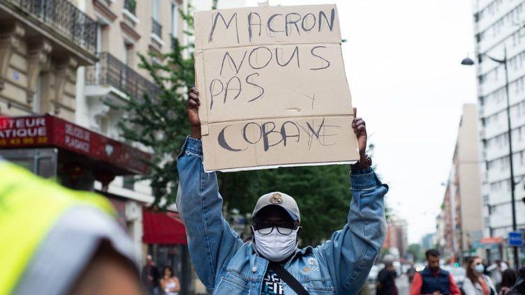 Un homme brandit une pancarte lors de la manifestation contre le pass sanitaire et l'obligation vaccinale, à Paris, le 17 juillet 2021. (DELPHINE LEFEBVRE / HANS LUCAS / AFP)