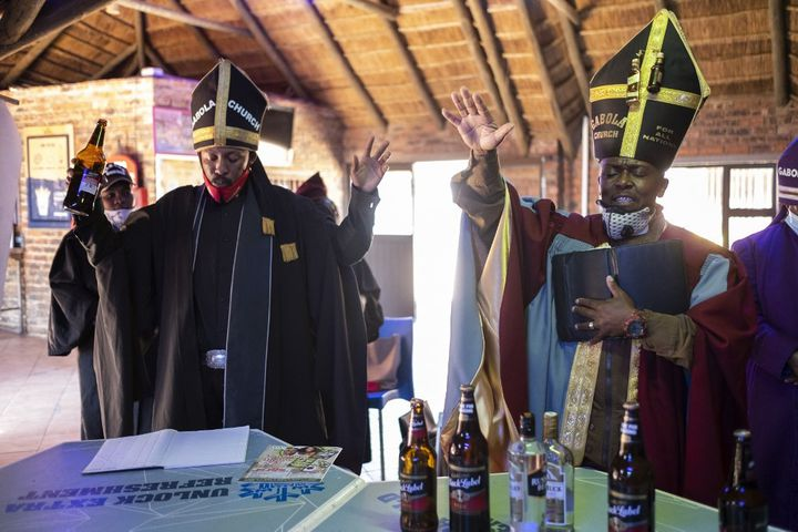 Tsietsi Makiti, fondateur de l'église Gabola, à droite sur l'image, en pleine célébration de la messe dominicale, dans la Bunny's Tavern, à Evaton. (WIKUS DE WET / AFP)