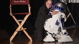 """Todd Fisher, le frère de Carrie Fisher, se penche sur le robot R2D2 de """"Star Wars"""", lors d'un hommage à la comédienne et à sa mère, Debbie Reynolds, le 25 mars 207 à Los Angeles (Etats-Unis). (KEVIN WINTER / GETTY IMAGES NORTH AMERICA)"""