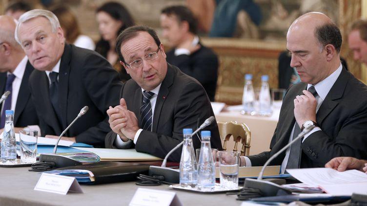 François Hollande, entouré de Jean-Marc Ayrault (à gauche) et Pierre Moscovici (à droite), lors d'un séminaire organisé à l'Elysée, à Paris, le 29 mai 2013. (CHARLES PLATIAU / AFP)