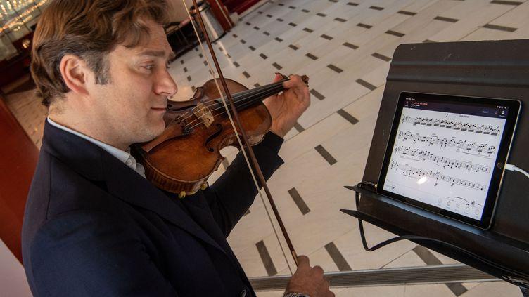 Renaud Capuçon jour avec la nouvelle application NomadPlay qui permet à un musicien de remplacer un instrument de l'orchestre sur une partition (CHRISTOPHE SIMON / AFP)