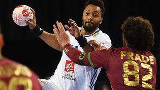 Le handballeur français Thimothey N'Guessan à la lutte avec la défense portugaise lors du match de qualification olympique, le 14 mars 2021, à Montpellier (Hérault). (SYLVAIN THOMAS / AFP)