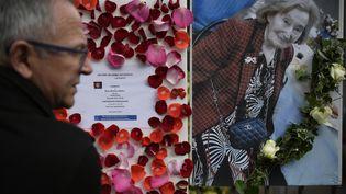 Un homme passe devant le portrait de Mireille Knoll, le 27 mars 2018 à Paris. (LIONEL BONAVENTURE / AFP)